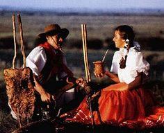 Cultura do Estado do Rio Grande do Sul=Brasil:churrasco(carne assada no fogo de chão) e chimarrão(bebida feita com erva-mate e água quente servida na cuia);o homem e a mulher estão com roupas que são tradição deste povo chamado de gaúcho.