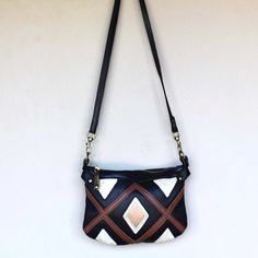 Black and brown Handmade leather cross body bag with hand cut geometric design on the front of the bag. Features a top zip closureand cross body strap. Black Handbags, Handmade Leather, Cross Body Handbags, Leather Crossbody Bag, Black And Brown, Bucket Bag, Hand Weaving, Shoulder Strap, Black Leather