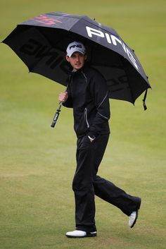 Matthew Nixon of England shelters from the rain under his umbrella before he hits his second shot on the 12th hole during Day 3 of the KLM Open at Kennemer G & CC on September 14, 2013 in Zandvoort, Netherlands.