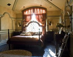 Antique vintage attic bedroom with four poster bed in creams and pinks and dark wood