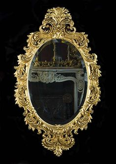 A highly ornate Rococo style giltwood antique oval wall mirror with a high stele crest above a luxuriously scrolled acanthus carved frame meeting a reversed stele crest below. French, late 19th century.