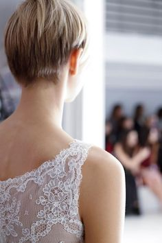 "A model awaits her turn at the Amsale Fall 2014 show to debut the ""Quinn"" gown with its French lace bodice, full skirt, lace under layer, and silk ribbon bow at the waist."