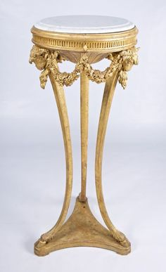With moulded fluted circular tops supported by three downswept moulded legs headed by rams' heads joined by swags of flowers and fruit and on cloven hoof feet and tricorn moulded plinths, height 13...