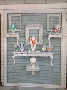 Love the all white props to help the colourful jewelry pop. Cool idea to mount light weight tables on a wall to bring the height of your display up. Could work in a craft fair booth. #jewellerydisplay