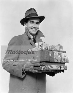 846-02797862 1930s 1940s MAN IN COAT HAT AND GLOVES HOLDING PILE OF WRAPPED…