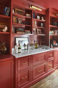 Designed to evoke lacquered chinoiserie, floor-to-ceiling cabinetry in ruby red anchors the second-floor front room—Angela's true living room—with a wet bar and illuminated display shelves. | Photo: Anthony Tieuli