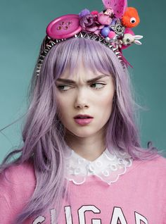 This image in general, the girl and the headband are all cheeky to the extreme. Everything from the purple hair to the oversized button says unique, unconventional, sassy and playful.
