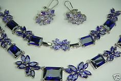 RETAILS FOR $300 IN THE VEGAS BOUTIQUES.......AS WITH ALL OUTSTANDING QUALITY CUBIC ZIRCONIA JEWELRY THIS SET COMES WITH A 1 AND 3/4 INCH NECKLACE EXTENDER.....THE EARRINGS MEASURE 1 INCH LONG AND ARE MADE UP OF A CONTRASTING TANZANITE LIGHT AND DARK CZ.....THEY ARE A FRENCH CLIP......THIS MAGNIFICENT NECKLACE MEASURES 17 INCHES......THAT BEING SAID - LET'S TRY OUR BEST TO DESCRIBE THIS WONDERFUL SET......TO CALL IT A FABULOUS FAKE DOESN'T QUITE DO IT JUSTICE.....DESIGNED TO LOOK EXACTLY…