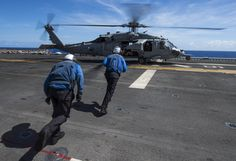 Aviation boatswain's mates run to prepare an MH-60S Sea Hawk helicopter for takeoff from the amphibious assault ship USS Boxer (LHD 4) in the Pacific Ocean, Sept. 4, 2013. (U.S. Navy photo by Mass Communication Specialist 2nd Class Kenan O'Connor/Released)