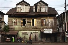 A pedestrian walks past a traditional colonial-era Board House dating back about a century on Pademba Road in Sierra Leone's capital Freetown April 27, 2012. REUTERS-Finbarr O'Reilly