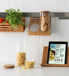 A display of a tablet stand, holder with containers, basket, all made of bamboo and hanging on a rail.