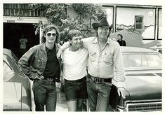 Clean-shaven and short-haired Willie Nelson, center, shortly after his relocation to Austin with Billy Joe Shaver's welcoming arm around him and Lee Clayton, left. Outside the entrance, Armadillo World Headquarters, Austin.