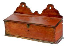 """Garth's Sale 1131 Lot 287 May 15 2015. Estimate $ 100-300. Sold for $1,050 (with premiums). AMERICAN HANGING CANDLE BOX. Mid 19th century, chestnut. Dovetailed with molded bottom board and shaped crest. Slant lift lid. Old worn red paint. Imperfections. 9.5""""h. 16.25""""w."""