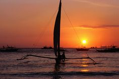 Paraw sailing, Sunset, Philippines  Paraw (traditional outrigger sailboat) sailing at sunset.      Dallas Stribley Lonely Planet Photographer  © Copyright Lonely Planet Images 2011