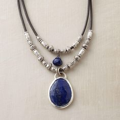 "TWOFOLD LAPIS NECKLACE -- Thai silver beads line up along the lengths of leather cord that ground our double lapis pendant necklace, a lapis gem dangling from each. Sterling silver gem settings and toggle clasp. Gem color and shape may vary. Handmade. Exclusive. Approx. 17""L."