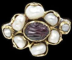 The garnet, pearls, clasped hands and floral shape presented by this lovely C17th Italian ring together symbolise passion, purity, marriage and love. (Victoria & Albert Museum)