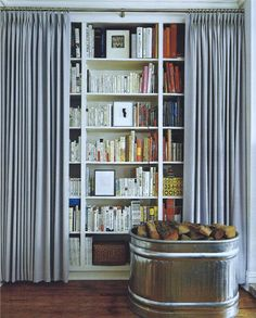 Library behind drapes by Todd Haley. Good idea for bedroom wall with window. Allows control of what you see... gives ability to simplify the room view with the pull of the curtain.