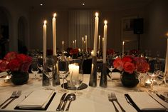 Event Scene Styling, long tables, bold coloured roses, silver & clear glass theme for candles. Elegant tall candle sticks, glittering t-lights, hurricane vase on round mirror with column candle as the centre.