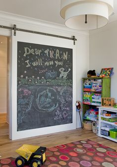 A chalkboard barn door on rails slides open to reveal playroom filled with distressed green bookcases stacked on top of each other beside a low white bookcase doubling as desk alongside a multi-color rug illuminated by a tiered drum chandelier. Chalk Wall, White Bookcase, Decor, Interior Barn Doors, Bedroom Wall, Playroom Design, Kids Room, Kids Playroom Decor, Home Decor