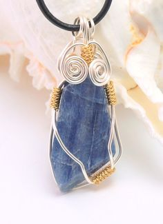 Silver and gold wire wrapped blue Kyantie pendant on black leather cord necklace at DesignedByDonnaD.etsy.com