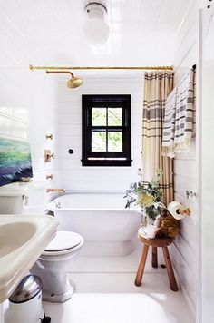 The bathroom of this Montauk home oozes vintage charm with a large soaking bath and brass fixtures. And how about that black-trimmed window?