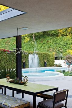 Beverly Hills landscape designed by Kameon, incorporates an outdoor dining set by Plain Air, chairs covered in fabric by Holly Hunt and benches covered in fabric by Trina Turk