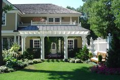 White pergola with sturdy pillars that match front covered porch and pillars - Decks & Structures | Sudbury Design Group