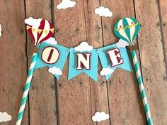 Up,up and Away! Somebodys turning one today! And this hot air balloon cake topper is the perfect way to decorate little ones cake. Banner is made from premium quality card stock with letters and pictures slightly elevated for a multidimensional look. Cake Topper features the word one but can be customized for any age up to five pennants.  Size:  Perfect size for smash cake or standard size cake. Packaged in clear bag for protection.  **Love the topper but it does not match you party colors?…