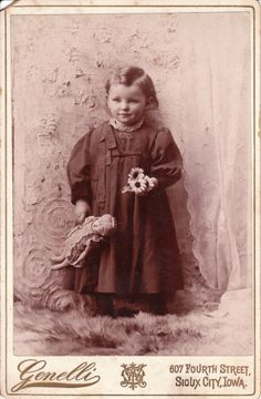 Antique photo of cute little girl with her doll and a nosegay of daisies circa 1910.