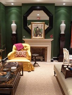 The deep hunter green walls in the Oscar de la Renta showcase room at Lee Jofa are a sharp and arresting background for the bright yellows,