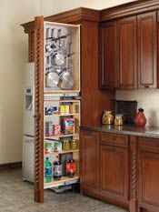 Got six inches of dead space in your cabinet wall? Put in a filler pullout organizer. This one has a pegboard panel for hanging pots & pans, above several shelves.