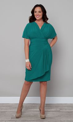 """Our plus size Danika Draped Dress is a vintage inspired piece that's haute and sultry.  This plus size dress has an asymmetrical line at the bottom waist for detail and a ruched torso to hide any tummy troubles. Add a brooch and a retro hairstyle to embody the """"good ol' days"""" perfectly.  #KiyonnaPlusSize #Plussize"""
