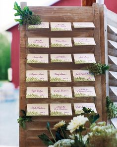 Rustic Seating Chart  Escort cards awaited their takers in the slats of old shutters leaned against hay bales.