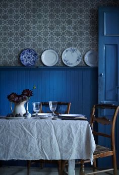 Like the bead board, plates on the rail, and the bright blue. The unhemmed tablecloth has got to go, however!