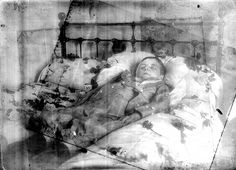 A boy in a sailors middy, positioned on a bed with flowers strewn about him. There doesn't appear to be any effort to make him look like he is just resting.