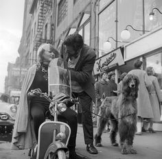 American jeweller, Sam Kramer helping one of his 'Space Girls' with her motorbike helmet on a Greenwich Village street. His clipped Afghan Hound waits for him patiently. 1955. (Getty Images)