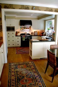 Wood floors, white cabinets, Persian rug - love this kitchen!