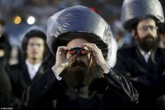 An ultra-Orthodox Jewish man uses binoculars during the wedding to catch a glimpse of the bride