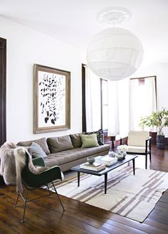 Living room with white walls, wood floors, patterned rug and pillows, brown couch, white chair, black coffee table, and large white light fixture