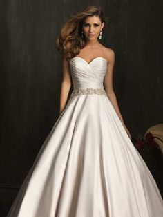 Allure Bridals, 9065; An exquisite ball gown in rich, soft satin. The strapless bodice features a sweetheart neckline, delicate ruching, and Swarovski crystals at the waistline.
