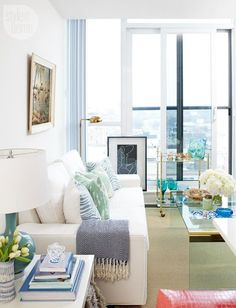 Brass, aqua, turquoise, a hint of kelly green and a spattering of flamingo pink against the neutral white backdrop lend a refined vintage tropical vibe to the main living area of homeowner Jennifer Collins's Toronto condo