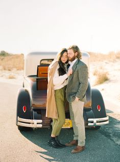 Unique engagement photo shoot of real couple with an antique Cadillac featuring red, green and neutral tones. #engagementphotoshoot #engagementphotography #engagementsessions #sophisticatedbride #elegantbridalinspiration
