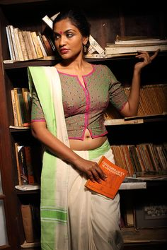Thumbapoo Blouse ~ Elapacha – Seamstress This blouse is our take on the iconic shirt blouse worn by fiery women writers and freedom fighters of Kerala. Classic and elegant like the women who wore them. The tiny coloured embroidery motifs on the leaf green blouse are reminiscent of the thumbapoo flower and add to its simple allure. Bright pink edging along the bodice and sides give it a bold contrast.