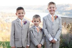 Ring bearers look sharp in gray suits with orange ties and purple bouts.Photo Credit: Angel Canary Photography