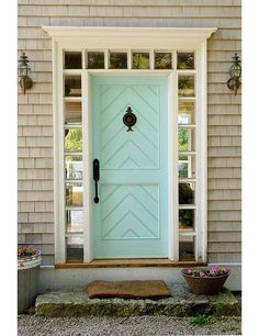"Coastal Charm: A front door can be a lovely way to pay homage to the home's locale. Here an inlaid chevron panel detail, duck's-egg blue color, and ship-lantern sconces all lend a seaside New England feel. Get more happy and cheerful interior design ideas on ""7 Fabulous Colorful Front Door Ideas"" on the One Kings Lane Style Guide!"