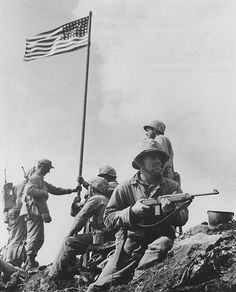 "The ""first"" flag raising at Iwo Jima by Marines of Easy Company 5th Marine Div. Feb 23, 1945."