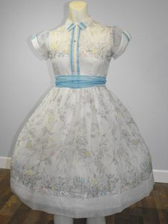 Dream will come true in this gorgeous vintage 1950s sheer white nylon voile fairy tale castle and princess novelty print party dress! Just perfect for a flower girl or the best birthday party dress EVER! Dress starts with semi fitted shirt waist styling, complete with baby blue and cream velvet ribbon trim on dress placket and trimmed on pointed short sleeves; dress then explodes in generous full circle skirt, shown here with a medium profile crinoline (not included in purchase), this dress…