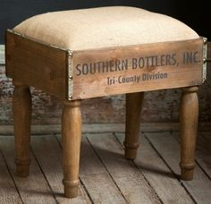 "Do you need a cute foot stool or side table? This vintage-inspired foot stool is made from a bottle crate and topped with a burlap covered cushion. 15 ¾"" Wide x 12"" Deep x 15 ½"" High Certain photograp"