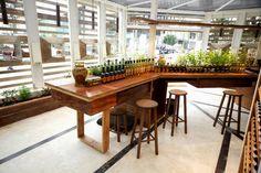 Artgusto loja e fabrica de massa fresca. Detalhe da horta na mesa central em madeira de demolicao. Piso em cimento queimado branco com listras de aco cortain.