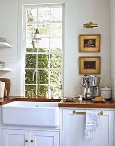 Cute kitchen design. Love the deep sink and the little picture gallery!